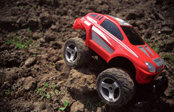 Toy off-road car. On ground overcoming obstacle, with slight vignette. Film scan Stock Photo