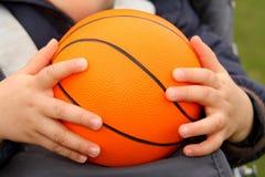 Toy Orange Ball. Toy orange basketball in boy´s hand Royalty Free Stock Photos