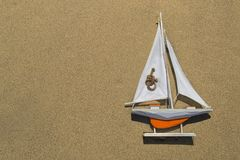 A toy orange ship with a white sail is lying on the textured sand on the right stock photo