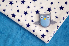 Toy owl rests on a child`s diaper Royalty Free Stock Images