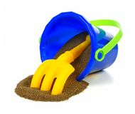 Toy pail with sand. Spilling toy sand pail with rake over a white background Stock Image