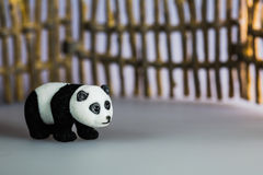 Toy panda in front of fence Stock Image