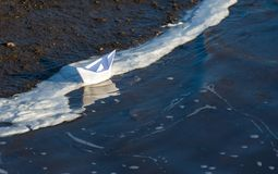 Toy paper boat on blue water at the edge of the shore covered with foam