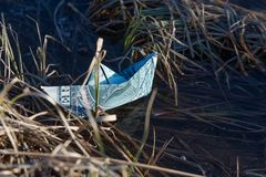A toy paper boat out of a dollar bill stuck in the undergrowth