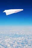 Toy paper plane flies over clouds Royalty Free Stock Images
