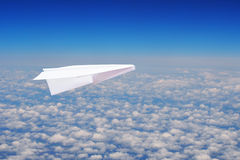 Toy paper plane flying over clouds Stock Image