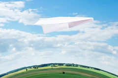 Toy paper plane flying over the Earth Royalty Free Stock Image