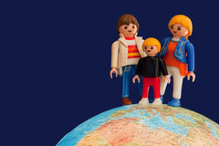 Toy parents and child standing on globe stock images
