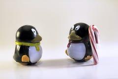 Toy Penguin Looking en otro con el bastón de caramelo rayado Imagenes de archivo