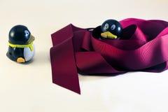 Toy Penguin Looking en otro envuelto en cinta del día de fiesta Imagenes de archivo