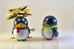 Toy Penguin Looking At Other avec l'arc de vacances sur la tête Photos libres de droits