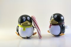 Toy Penguin Looking at Other with Candy Cane. Toy Penguin Looking at Other with Christmas Candy Cane Royalty Free Stock Photo