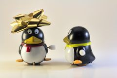 Toy Penguin Looking At Other con el arco de Navidad en la cabeza Foto de archivo libre de regalías