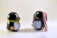 Toy Penguin Looking at Other with Striped Candy Cane Stock Images