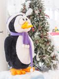 A toy penguin standing against Christmas trees surrounded with gift boxes. stock photography