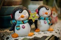 Toy penguin wearing headphones on shelf Stock Photos