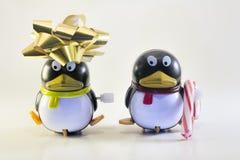 Toy Penguins con el arco del día de fiesta y el bastón de caramelo Foto de archivo libre de regalías