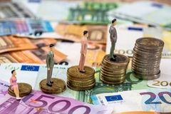 Toy people standing on euro coins and banknotes stock photo