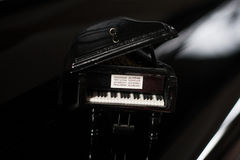 Toy piano. Small black toy piano on the real piano Royalty Free Stock Photo