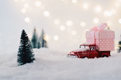 Toy pickup car carrying Christmas present. In the snow Royalty Free Stock Image