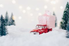 Toy pickup car carrying Christmas present. In the snow Stock Image