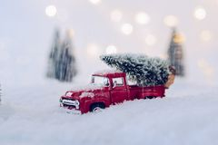 Toy pickup car carrying Christmas tree. In the snow Royalty Free Stock Photos