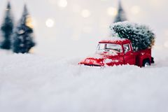 Toy pickup car carrying Christmas tree. In the snow Stock Photos