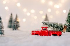 Toy pickup car carrying Christmas tree. In the snow Stock Image