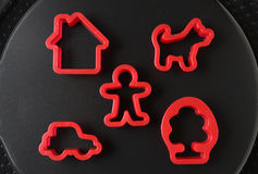 Toy pie mould on  black background. Set of molds for plasticine. Toy pie mould on  black background. icons in the form of man, house, dog, car and tree Stock Photos