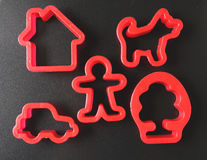 Toy pie mould on  black background. Set of molds for plasticine. Toy pie mould on  black background. icons in the form of man, house, dog, car and tree Royalty Free Stock Photography