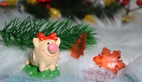Toy pig and winter decor, congratulations on the holiday. Symbol of the year of the pig on the background of Christmas stock image