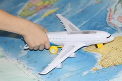 The toy plane flies by the geographical map. The plane is held by a child. The liner in his hand flies over the world map. Travel by plane stock photo