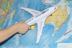 The toy plane flies by the geographical map. The plane is held by a child. The liner in his hand flies over the world map. Travel by plane royalty free stock image