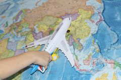 The toy plane flies by the geographical map. The plane is held by a child. The liner in his hand flies over the world map. Travel by plane stock images