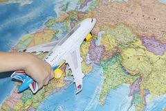 The toy plane flies by the geographical map royalty free stock image