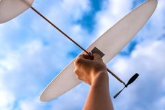Toy plane in woman`s hand in sky. royalty free stock images