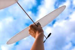 Toy plane in woman`s hand in sky. stock photography