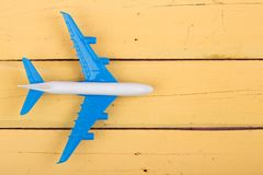 Toy plane on yellow wooden background stock images
