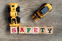 Toy plastic bulldozer hold toy block letter s to word safety. Toy plastic bulldozer hold toy block letter s to fulfill word safety with foklift on wood Stock Photo