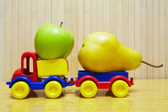 Toy plastic car with apple and pear Royalty Free Stock Image