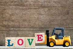 Toy plastic forklift hold block E to compose word love. Toy plastic forklift hold block E to compose and fulfill wording love on wood background royalty free stock image