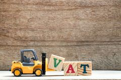 Toy plastic forklift hold block V to compose word VAT. Toy plastic forklift hold block V to compose and fulfill wording VAT on wood background stock photos