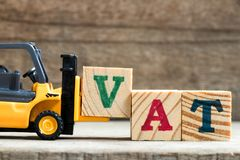 Toy plastic forklift hold block V to compose word vat. Toy plastic forklift hold block V to compose and fulfill wording VAT on wood background royalty free stock image
