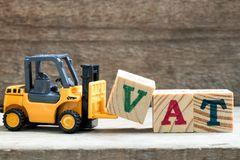 Toy plastic forklift hold block V to compose word VAT. Toy plastic forklift hold block V to compose and fulfill wording VAT on wood background royalty free stock photography