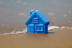 Toy plastic house on the sand Stock Photo