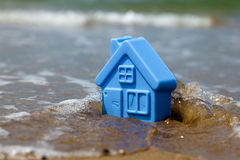 Toy plastic house on the sand Stock Images