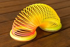 Toy plastic rainbow on a wooden table. Multi-colored spiral for stock image