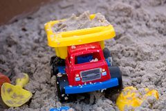 Toy Plastic Truck in the Sand. Yellow, Blue, and Red Toy Plastic Truck in the Sand stock image