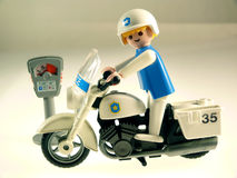 Toy policeman on bike. Checking parking meter Stock Photography