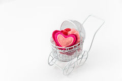 Toy pram with wool heart  on white background. Valentine's Day or Newborn Greeting Card. Royalty Free Stock Photo